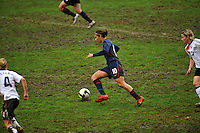 Carli Lloyd dices through the muddy field. The USA captured the 2010 Algarve Cup title by defeating Germany 3-2, at Estadio Algarve on March 3, 2010.