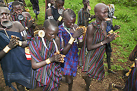 """Ethiopia. Southern Nations, Nationalities, and Peoples' Region. Omo Valley. Mursi tribe. Agro-pastoralist group. Nomadic. A group of Mursi women clap their hands in a welcoming sign for foreign visitors. Mursi women are known as """"disk-lip"""" women. The bottom lip is slit along its full length and the front bottom row of teeth are pulled out to accomodate the ceramic disk which is handmade with a rim around which the stretched lip is pulled. The women are famed for wearing large plates in their lips (round clay plates placed into a cut in the lower lip) and ears. The disk is seen as a symbol of beauty and wealth, and often the younger girls will pierce and strech their ear-lobes, inserting a matching disk in the extended lobe. The Omo Valley, situated in Africa's Great Rift Valley, is home to an estimated 200,000 indigenous peoples who have lived there for millennia. Amongst them are 8'000 Mursi who dwell between the Omo and Mago rivers. Southern Nations, Nationalities, and Peoples' Region (often abbreviated as SNNPR) is one of the nine ethnic divisions of Ethiopia. 11.11.15 © 2015 Didier Ruef"""