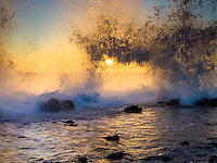 Waves crash against the rocky shoreline of Keahole Point, with the sunset in the background, Big Island.