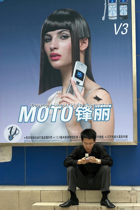 A man checks his mobile phone in front of a billboard of Motorola in Beijing, China..30 May 2005