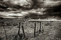 Sepia toned black and white image of Cerro Guadalupe, Cabezon Peak, and Cerro Santa Clara in the Rio Puerco Valley in the San Juan Basin of northwestern New Mexico under a stormy sky at sunset.