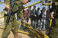 An Israeli soldier opens the gate of the fence as Palestinian school children to cross the new separation fence at the Palestinian town of Jbarah, in the West Bank. Jbarah, a Palestinian town with about 300 habitants was left on the Israeli side of the fence, without schools in the town, Palestinian children of Jbarah have to cross the fence through the gate two times a day, when Israeli soldiers open it for them to cross.Photo by Quique Kierszenbaum