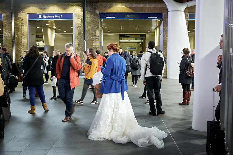 Bride waiting for train at Kings Cross station London.