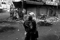 A mother carries her child past a group of Israeli soldiers during a confrontation in the center of Hebron, Palestine.
