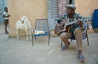 "Mali. Bamako. The musician Boubacar Traore ""Karkar"" plays the guitar and sings in his home courtyard. © 1997 Didier Ruef"
