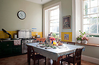 A souvenir portrait of Queen Victoria hangs above the bright yellow tiles that line the walls of the kitchen