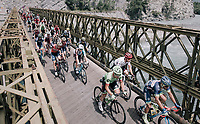 peloton riding over a narrow old bridge in the neutralised section of the race<br /> <br /> 104th Tour de France 2017<br /> Stage 19 - Embrun › Salon-de-Provence (220km)
