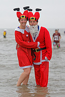 Pictured: A couple in Santa costumes. Tuesday 25 December 2018<br /> Re: Hundreds of people take part in this year's Porthcawl Christmas Swim in south Wales, UK.