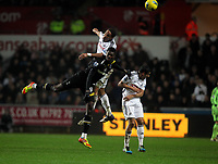 Pictured: Ashley Williams of Swansea (TOP) heads the ball over Emmanuel Adebayor of Tottenham Hotspur.  Saturday 31 December 2011<br /> Re: Premier League football Swansea City FC v Tottenham Hotspur at the Liberty Stadium, south Wales.