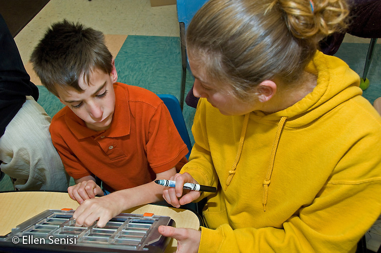 MR / Albany, NY.Langan School at Center for Disability Services .Ungraded private school which serves individuals with multiple disabilities.Teaching assistant and student interact as she helps him use an alternative and augmentative communication device during speech and language development lesson.Boy: 9, cerebral palsy.MR: Cam10, Mye2 .© Ellen B. Senisi