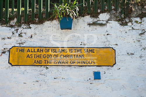 "Shimla, Himachal Pradesh, India. The Toy Train railway sign: ""The Allah of Islam is the same as God of Christians and the Iswar of Hindus."""