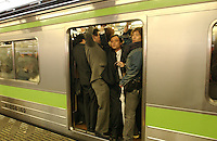Commuters during rush hour in Shinjuku Station squeeze into packed trains. Shinjuku is the busiest station in the world..Mar 2002