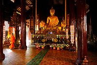 Tall Sitting Buddha covered with gold in a Buddhist temple in Chiang Mai city, Thailand, Southeast Asia. Buddha may be pictured in number of different poses. Most usually he is seated cross legged, which indicated meditation. One Buddhist monk wearing an orange robed Mahanikai traditional clothe is walking on the side on the temple.