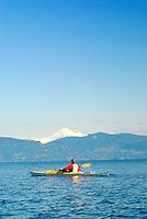 Male paddler in yellow kayak and red PFD paddling in San Juan Islands with Mount Baker visible in background, Sea Kayaking the San Juan Islands, WA.