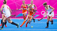 29 JUL 2012 - LONDON, GBR - Carlien Dirkse van den Heuvel (NED) of The Netherlands (centre) weaves between Belgian players as she makes her way upfield during their women's London 2012 Olympic Games Preliminary round hockey match at the Riverbank Arena in the Olympic Park in Stratford, London, Great Britain .(PHOTO (C) 2012 NIGEL FARROW)