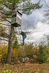 Hunter climbing down from his homemade hunting blind after making a preseason safety check.
