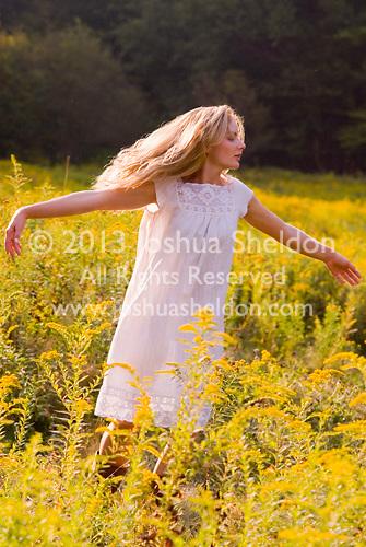 Blonde woman wearing white dress in field of goldenrod