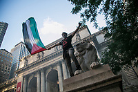 NEW YORK, NY - JUNE 15: A Pro-Palestine man waves a flag next to the New York Public Library during a large protest in New York on June 15, 2021. The solidarity action of hundreds of pro-Palestinians is a form of support against attacks carried out by the Israeli government. At the same time, Palestinian Prime Minister Mohammad Shtayyeh says the new Israeli government is just as bad as the old one and condemns Naftali Bennett's announcements in support of Israeli settlements. That is why the demonstrations continue in different parts of the world. (Photo by Pablo Monsalve / VIEWpress via Getty Images
