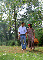 A romantic teenage couple strolls barefoot in the woods with a picnic basket.