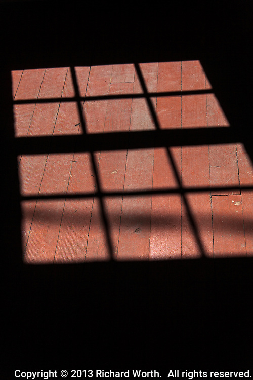 A 2013 window frame shadow falls across an 1800s red wooden floor. Time travel at the Bridge Tender's House, Fort Steele, Wyoming.