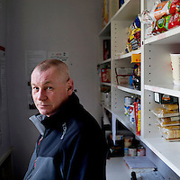 Stuart Hudson, manager of a distribution centre which supplies 27 foodbank centres around County Durham in the northeast of England.<br /> <br /> 'There is a full spectrum at food banks, you can't stereotype people who need a foodbank. We all have a mortgage and a bank loan and if you lose your job, it doesn't take long to be in the same boat…. <br /> <br /> We are looking after a family group who are victims of trafficking and they are not entitled to benefits whatsoever. Two are pregnant and they have two small children, so we will support them for a short time…. and then teach them how to put money away for hard times when their jobs aren't paying….<br /> <br /> Quite a bit of it as well is poor money management, dealing with debts, summer holidays and christmas. Some people have to be relocated due to domestic violence, people split up, when things like that happen, its usually the one left with the kids, their bank accounts have been cleared out. We see people with nice cars and houses but no money to put food on the table. It's very hypocritical of the job centre to say you're sanctioned and here is the letter for the foodbank….<br /> <br /> I look after 27 centres in Country Durham, with a couple of hundred volunteers.  Some are in churches, some in community centres…. <br /> <br /> You are trying for the food bank to be a triage service with high, medium and low need.  Maybe people get crisis loans when sanctioned and it's teaching them how to manage until that loan is paid back.'