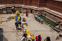 Nepal, Kathmandu, people lined up with water containers at the fountain for water Durbar Square.