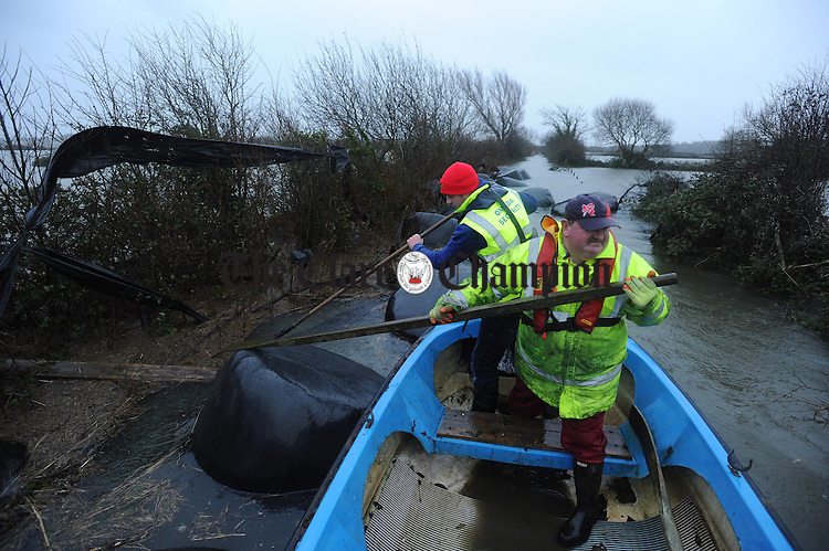 Floating Harvest.....Gerry Murtagh and his son Damien assess the damage to their summer harvest of silage bales after over 20 acres of their farm got flooded at Lacknashannagh, Kildysart on the Shannon Estuary. Photograph by John Kelly.