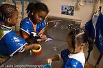 Preschool Headstart 3-5 year olds water table three girls wearing smocks playing   horizontal