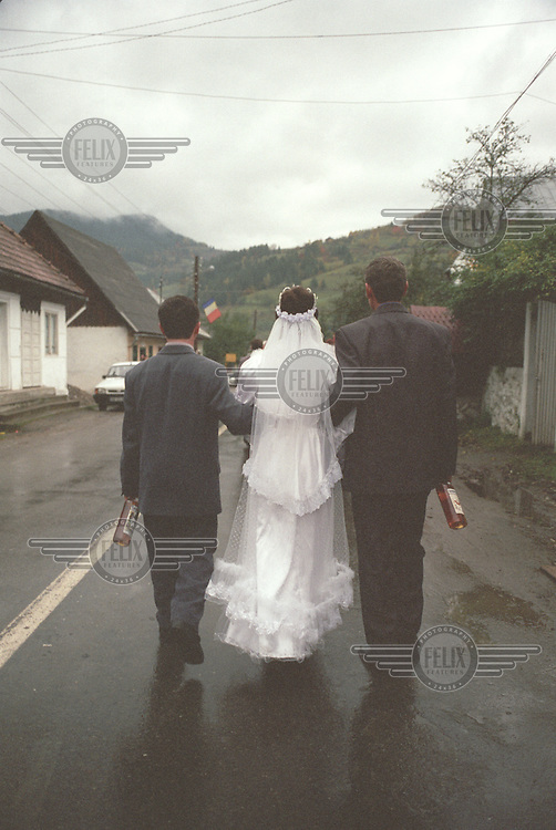 ROMANIA. Horea. 12 October 2002..A wedding procession walks through the village of Horea after a marriage ceremony conducted by Corneliu Olar, the local Mayor..©Andrew Testa / Panos Pictures
