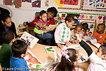 Education preschool 4 year olds books and reading two female teachers working with separate children as groups of boys and girls look at books horizontal