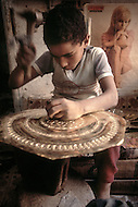 In Casablanca, Morocco, children are employed to engrave copper plate. Child labor as seen around the world between 1979 and 1980 - Photographer Jean Pierre Laffont, touched by the suffering of child workers, chronicled their plight in 12 countries over the course of one year.  Laffont was awarded The World Press Award and Madeline Ross Award among many others for his work.