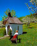 Deutschland, Bayern, Oberbayern, Chiemgau: Frau ruht auf Bank vor Kapelle, Blumenwiese und Apfelbluete | Germany, Bavaria, Upper Bavaria, Chiemgau: woman sitting on bench, chapel, flower meadow and fruit tree blossom