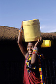 Lolgorian, Kenya. Siria Maasai Manyatta; smiling Maasai outside a mud walled house carrying a yellow plastic barrel on her head