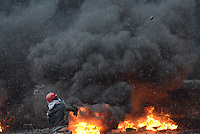 A rioters throws stones  against police trucks during the   protest against new draconian law to ban the right to  protest across the country.  Kiev. Ukraine