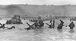 FILE - In this June 6, 1944 file picture, some of the first assault troops to hit the Normandy, France beachhead take cover behind enemy obstacles to fire on German forces as others follow the first tanks plunging through the water towards the German-held shore during World War II. (AP Photo)