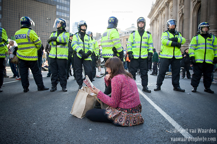 A loan protester reads Chomsky in front of the police line. Climate Camp in the City - G20 - London (©Robert vanWaarden)