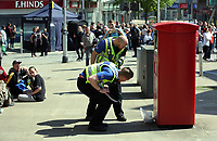 Pictured: Two police officers examine an unattended package left by a post box in Union Street, Swansea Wednesday 24 May 2017<br />Re: The Quadrant shopping centre in Swansea has been evacuated following reports of a suspicious package being found.<br />The bus station and Swansea Indoor Market have also been closed as part of the evacuation.