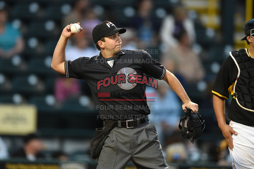 Home plate umpire Joe George throws a ball to the pitcher during a game between the Jupiter Hammerheads and Bradenton Marauders on April 19, 2014 at McKechnie Field in Bradenton, Florida.  Bradenton defeated Jupiter 4-0.  (Mike Janes/Four Seam Images)