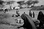 Somali refugees gather to collect water from a communal water tap in the Dagahaley refugee camp in the Dadaab refugee camp in northeastern Kenya. Hundreds of thousands of refugees are fleeing lands in Somalia due to severe drought and arriving in what has become the world's largest refugee camp. Photo: Sanjit Das/Panos