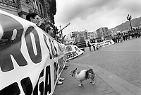 """Spain. Basque Country. Spain. Basque Country. Bilbao is the largest city in the province of Biscay and in the Basque Country as a whole. Demonstration by members of """"Senideak"""" in front of Bilbao's theater. A small dog stands by the protestors. Etxerat, originally called Senideak ('Relatives' in Basque), was created on 6 October 1991. Etxerat (Basque: meaning 'Homeward') is an association of family members of people who have been imprisoned or exiled because of their activity in support of the Basque National Liberation Movement. Most of those prisoners and exiles are members, or former members, of the Basque armed terrorist organization ETA. Others were not members of ETA but have been jailed for collaborating with it, or have been convicted of other crimes such as belonging to illegal organizations like SEGI or Gestoras pro Amnistía, belonging to or trying to rebuild banned political parties such as Batasuna and Askatasuna, participating in Kale borroka, or for the """"public glorification of terrorism"""". Etxerat's primary activities are to support those family members, and to campaign to defend the rights of their imprisoned and exiled relatives. The Basque Country (Euskadi, País Vasco, Pays Basque), officially the Basque Autonomous Community (Euskal Autonomia Erkidegoa, Comunidad Autónoma Vasca, CAV) is an autonomous community in northern Spain. It includes the Basque provinces of Álava, Biscay, and Gipuzkoa. The Basque Country or Basque Autonomous Community was granted the status of nationality within Spain, attributed by the Spanish Constitution of 1978. The autonomous community is based on the Statute of Autonomy of the Basque Country, a foundational legal document providing the framework for the development of the Basque people on Spanish soil. 25.03.92 © 1992 Didier Ruef"""