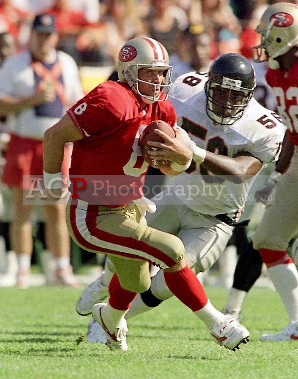 San Francisco 49ers quarterback Steve Young (8) scrambles for a 6-yard touchdown as Atlanta Falcons linebacker Jessie Tuggle (58) tries to bring him down during second quarter action at Candlestick Park in San Francisco, Oct. 13, 1991. (Photo by Alan Greth)