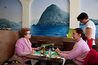 Switzerland. Canton Ticino. Lugano. Angelica Vukmirovic ( 52 years old) is a waitress working at the Pestalozzi restaurant.  She is taking the orders from two women who came for lunch. A painting on the wall from the lake Lugano and the mountains covered with forests. 14.04.13. © 2013 Didier Ruef