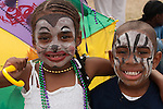 Two black children with their faces painted for Mardi Gras at the  Bayou Festival at the Queen Mary Event Park, Long Beach, CA