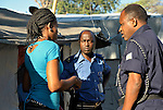"""A woman in the Petionville Camp at the edge of Port au Prince, Haiti, is interviewed by police officials after lodging a domestic violence complaint against her husband. Some 50,000 residents are packed onto what was once a golf course, and the close quarters and frustration at lack of employment and other opportunities contributes to tensions, according to Pascal Rwatangabo (right), a Rwandan officer with the United Nations MINUSTAH police force. """"With nothing to do but sit in their tent all day under the sun, it's not surprising to see problems,"""" Rwatangabo said. """"And when the men start drinking, it's even worse. Yet when we start to arrest a man for a violent crime, the woman will often plead with us to let him go, because she realizes her precarious economic situation will deteriorate if the man is not there, even though his violent behavior may continue."""" Also present was MINUSTAH official Aphrodis Nkandineza (center). The Petionville Camp is the largest camp of hundreds of locales hosting more than a million people left homeless by the January 12, 2010 quake."""