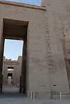 "View through the doorway of the First Pylon at the mortuary temple of Ramses III at Medinet Habu at Thebes.Thebes was the ancient capital of Egypt and was built in and around modern day Luxor.The ancient name for Medinet Habu was Djamet meaning ""males and mothers."" Its holy ground was believed to be where the Ogdoad,the four pairs of primeval gods,were buried.Medinet Habu was both a temple and a complex of temples.Queen Hatshepsut who ruled Egypt from 1479-1458 BC  and Tuthmosis III who reigned from 1479-1425 BC built a small temple to Amun on the site of an earlier structure. Next to their temple, Ramses III who reigned from 1186-1155 BC built his mortuary temple.He then enclosed both structures within a massive mud-brick enclosure.The temple precinct measures about 700 feet by 1000 feet and contains more than 75,350 sq ft of decorated surfaces across its walls.It is the best preserved of all the mortuary temples of Thebes."