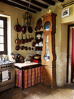 In the kitchen, the long case of an old clock has been appropriated as a place to store table linen