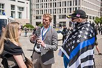 """Die der Gruppierung """"Patriotic Opposition Europe"""" des italienischen Rechtsextremisten Eric Graziani Gruenwald veranstaltete am Samstag den 6. Juni 2020 auf dem Pariser Platz in Berlin-Mitte eine Kundgebung um fuer """"Grundrechte"""" zu demonstrieren. Es wurden Reden gehalten, die zum Widerstand gegen die Bundesregierung und Angela Merkel aufriefen und in denen die Covid 19-Pandemie und die Massnahmen zur Eindaemmung der Pandemie als Verschwoerung gegen die Bevoelkerung bezeichnet wurden und die Bevoelkerung mit Zwangsimpfungen, der 5G-Mobilfunktechnik sowie durch Bill Gates unterdrueckt werden soll. <br /> Es kamen ca. 60 Menschen aus verschiedenen Bundeslaendern.<br /> Im Bild: Ein Kundgebungsteilnehmer mit einem Basecap mit der Aufschrift """"Make America Great Again"""" und einer umgehaengten Fahne der rechten US-Polizistenorganisation """"Blue Lives Matter"""" beschimpft eine Gegendemonstrantin, dass """"die Schwarzen"""" selber rassistisch"""" seien, da sie gegen Weisse protestieren. Aufgenommen wird dies vom rechtsextremen und antisemitischen Videoaktivisten Nikolai Nerling alias """"Der Volkslehrer"""".<br /> """"Blue Lives Matter"""" wurde im Dezember 2014 von rechten und rassistischen Polizisten in der USA als Gegenorganisation zur afroamerikanischen """"Black Lives Matter""""-Bewegung gegruendet.<br /> 6.6.2020, Berlin<br /> Copyright: Christian-Ditsch.de<br /> [NUR FUER REDAKTIONELLE ZWECKE! Werbung nur auf Anfrage beim Fotografen. Inhaltsveraendernde Manipulation des Fotos nur nach ausdruecklicher Genehmigung des Fotografen. Vereinbarungen ueber Abtretung von Persoenlichkeitsrechten/Model Release der abgebildeten Person/Personen liegen nicht vor. NO MODEL RELEASE! Don't publish without copyright Christian-Ditsch.de, Veroeffentlichung nur mit Fotografennennung, sowie gegen Honorar, MwSt. und Beleg. Konto: I N G - D i B a, IBAN DE58500105175400192269, BIC INGDDEFFXXX, Kontakt: post@christian-ditsch.de<br /> Bei der Bearbeitung der Dateiinformationen darf die Urheberkennzeichnung in den EXIF- und  IP"""