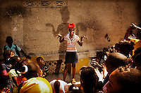 "My-Taelle does a clown routine in front of a group of children..My-Taelle is 10 years old. She lives with her mother, two brothers and four sisters. Her father left the family home. My-Taelle in in fifth grade. Like many other children in Haiti she wasn't able to go to school following the 2010 earthquake. She was happy to be back at school when a temporary classroom was set up because this seemed like normality was returning to her life. ""I dream of becoming a clown. I'll be able to make other children happy. Many people were sad after the earthquake because they lost family members or their houses. I'm glad that I can make people laugh.""."