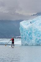 Paddle boarding among icebergs in Bear Glacier Lagoon, Kenai Fjords National Park, southcentral, Alaska.