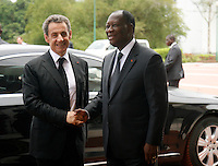 Ivorian president Alassane Ouattara(R) welcomes former French president Nicolas Sarkozy(L) upon his arrival for a meeting at the presidential palace in Abidjan, on March 18, 2016.